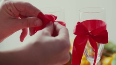 Hands tied red bow on a transparent glass of champagne Stock Footage