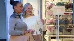 Women discuss bras and panties near the lingerie shop Stock Footage