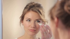 Lady smears cream on the eyes Stock Footage