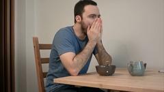 Sleepy man yawning at breakfast table Stock Footage
