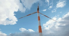 Large wind turbine spinning with clouds in the background Stock Footage