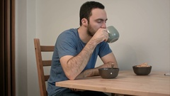 Sad and frustrated man drinking tea sitting at the kitchen table Stock Footage
