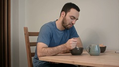 Young man having no appetite for his breakfast Stock Footage