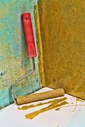 Roller paintbrush near grunge yellow painted wall. Stock Photos