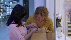 Woman suprises her friend by her purchases Stock Footage