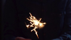 Man holding bright festive Christmas sparkler in hand Stock Footage
