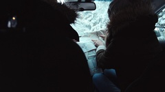 Friends traveling together by car in winter, looking for the right way on map Stock Footage