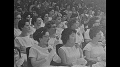 Vintage 16mm film, 1957 grad ceremony, audience claps, students accept trophies Stock Footage