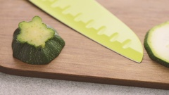 Sliced zucchini on wooden cutting board. Food preparation film clip. Stock Footage