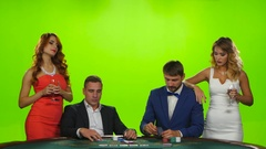 Two pairs of young people playing cards at poker table Stock Footage