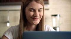 Beautiful attractive casual young woman sitting in a kitchen and talking with a Stock Footage
