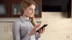 Beautiful young woman with a phablet standing in kitchen. Browsing Internet and Stock Footage