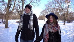 Man and Woman walking on snow in winter park taking hands romantic day Stock Footage