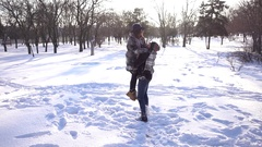 Young man and woman love, kissing and having fun in the winter day park on snow Stock Footage