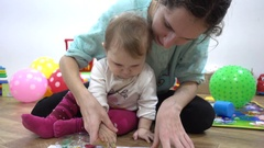 Mother and child baby girl playing with paints of different colors painting arms Stock Footage