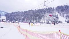 BUKOVEL, UKRAINE -: Snowboarder and skiers enjoying on slopes Stock Footage