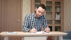 Happy student finishing writing his essay Stock Footage