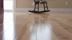 Dolly shot of a childs rocking chair on a hardwood floor Stock Footage