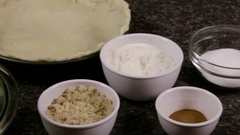 Apple pie filling and ingredients beside pie crust and pan Stock Footage