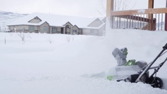 Dolly shot of a man snowblowing the driveway after storm Stock Footage
