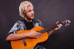 Blonde man playing acoustic guitar Stock Photos
