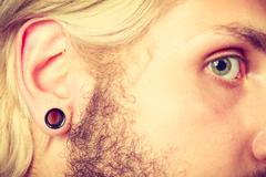 Pierced man ear, black plug tunnel Stock Photos
