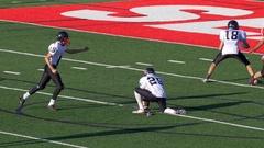 A football kicker prepares to kick the ball. Stock Footage