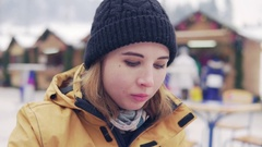 Beautiful blonde eats pilav against background of winter market Stock Footage