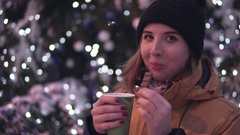 Dreaming young woman with hot tea and peace of chocolate near christmas tree Stock Footage