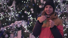 Laughing young woman with hot tea and peace of chocolate near christmas tree Stock Footage