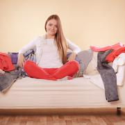 Woman sitting on sofa in messy room at home. Kuvituskuvat