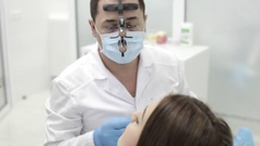 Dentist makes the procedure. Beutyful young woman visit a modern dental clinic. Stock Footage