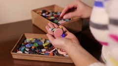 The girl considers different plastic clothing buttons. Stock Footage