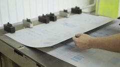 Close up hands hole puncher working inside printing house Stock Footage