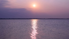 Sun shines over lake or river forming sun path on water Stock Footage