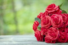 Close up beautiful red roses bouquet with glowing light background for vale.. Stock Photos
