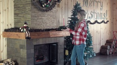 Woman decorating fireplace for Christmas Stock Footage
