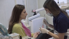 Dentist makes procedures and treat teeth for a beautiful patient woman in dental Stock Footage