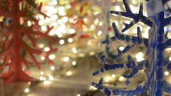 Christmas decorative Christmas trees on the background of bright garland. Stock Footage