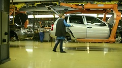 People work at assembly of cars LADA Kalina on conveyor of factory AutoVAZ Stock Footage