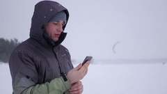 Man makes selfie, choose a convenient angle, against the backdrop of snow Stock Footage