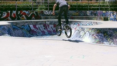A young man rides a BMX bicycle in a concrete skate park, slow motion. Stock Footage
