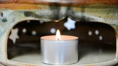 Tea light burning in a ceramic teapot warmer Stock Footage