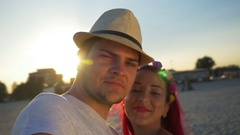 Beautiful lovers kissing and filming themselves on the beach at sunset Stock Footage