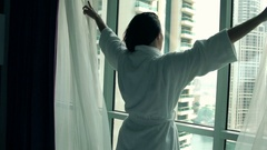 Woman in bathrobe unveil curtains and admire view from window at home Stock Footage