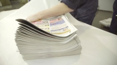 Pile of finished newspapers is wrapped in printing plant Stock Footage