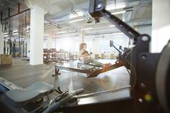 Workout on rowing machine Stock Photos
