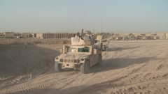 Squad in armored military vehicles driving through desert Stock Footage