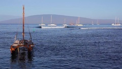 Hawaiian Canoe in harbor, surfer riding a wave, and the Hokulea in the distance. Stock Footage