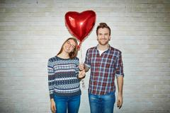 Happy couple holding symbol of love - red heart-shaped balloon Stock Photos